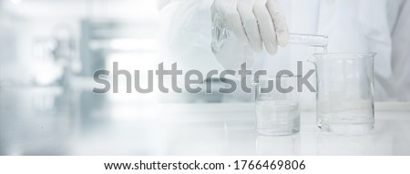 scientist in white coat poring water into glass beaker in medical laboratory science banner background