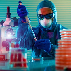 scientist man in a protective medical mask and gloves makes PCR DNA coronavirus tests in a modern  bacteriological laboratory.