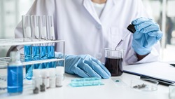 Scientist or medical in lab coat holding dropper with reagent, mixing reagents in glass flask, glassware containing chemical liquid, laboratory research and testing of Microscope.