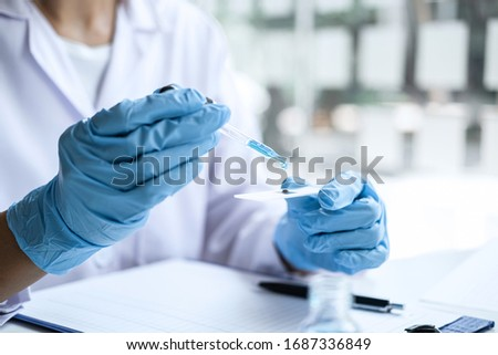 Scientist or medical in lab coat holding test tube with reagent, mixing reagents in glass flask, glassware containing chemical liquid, laboratory research and testing of Microscope.