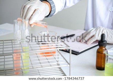 Scientist or medical in lab coat holding test tube with reagent, mixing reagents in glass flask, glassware containing chemical liquid, laboratory research and testing.