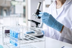 Scientist or medical in lab coat working in biotechnological laboratory, Microscope equipment for research with mixing reagents in glass flask in clinical laboratory.