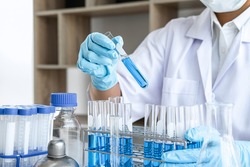 Scientist or medical in lab working in biotechnological laboratory using equipment for research with mixing reagents in glass flask in clinical laboratory.
