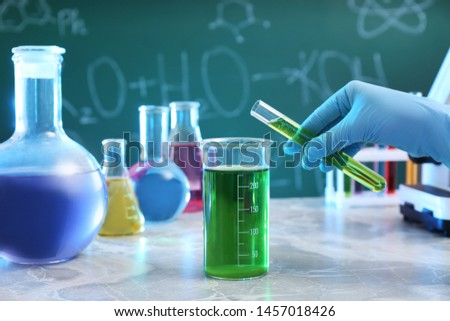 Scientist pouring liquid into beaker at table against chalkboard, closeup. Chemistry glassware