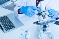 Scientist, researcher, technician or student wear blue rubber gloves while using a microscope in a modern laboratory. Education Chemistry and science medical research concept.