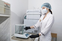 Scientist weighing chemicals by digital scales in grams in chemical laboratory