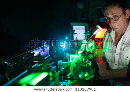 Scientist with glass demonstrate laser of microparticles, front