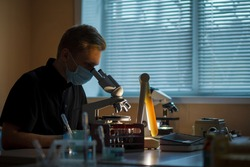 Scientist working in lab. Doctor making microbiology research. Laboratory tools: microscope, test tubes, equipment. Coronavirus covid-19 , bacteriology, virology and health care.