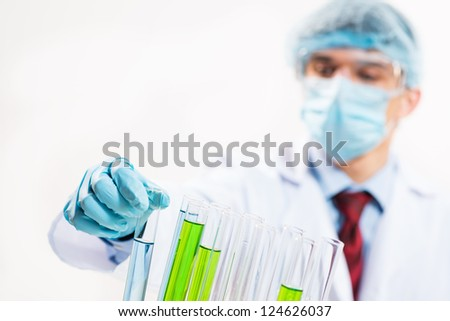 scientist working in the lab examines a test tube with liquid