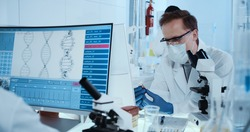 Scientist working with microscope in futuristic laboratory. Genetic research