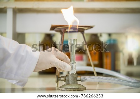 Scientists are adjusting the air to the bunsen burner to provide more complete combustion in the chemical laboratory.