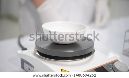 Scientists are boiling chemicals in a volatile bowl on hot plate stirrer. In chemical laboratory