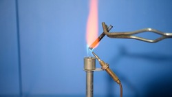 Scientists are burning natural rubber in a culture tube to test the physical properties of natural rubber. In a chemical laboratory