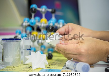 Scientists are folding filter paper for use in chemical filtration, Capillary tubes Stock photo ©