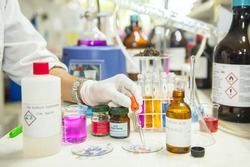 Scientists are investigating the acidity of a chemical by litmus paper in a chemistry lab.
