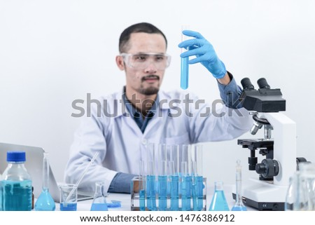 Scientists are studying laboratory chemicals, blue chemicals in tube