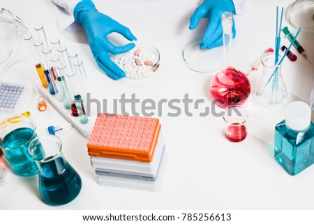 scientists holds pill in hand in laboratory. drug discovery, pharmacology and biotechnology concept. science and medical research background with blood sample. top view and copy space.