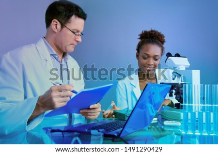 Scientists, senior Caucasian male and young African female, work together on a joint microscope project in histopathology research facility