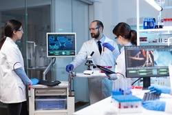 Scientists working In laboratory discovering genetic infection because of rare disease. Chemists in pharmaceutical lab examining sample for medical experiment with technology for medicine industry.
