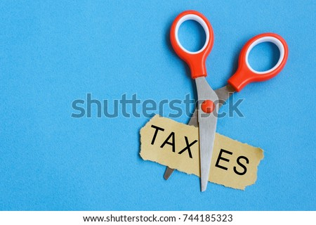 Scissor cutting the word 'taxes' in a piece of paper.