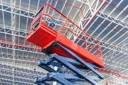 Scissor lift platform with hydraulic system elevated towards a factory roof with construction workers, Mobile aerial work platform