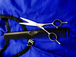 Scissors and comb on a blue background. Hairdressing tools on a blue cape. Set of hairdressing tools for a beauty salon. Scissors and comb.