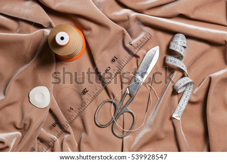 Scissors and sewing accessories on a beige fabric background. Top view.