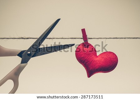 Scissors cutting a rope with a red heart - Broken heart concept