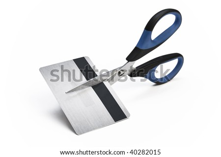 Scissors cutting credit card in halves