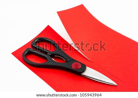 Scissors cutting red paper in two parts