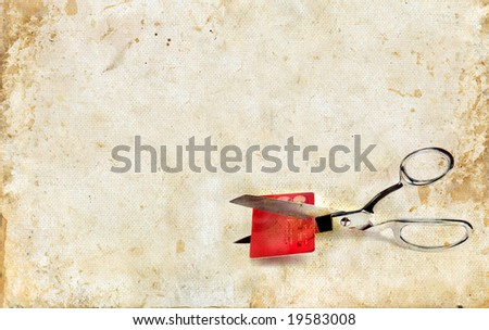 Scissors cutting up a credit card on a grunge background. Copy-space for your text.