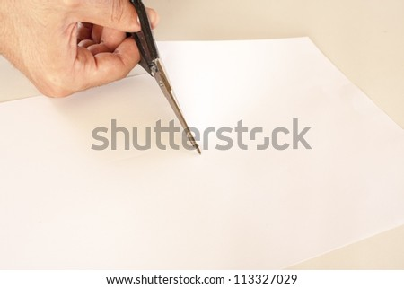 scissors cutting white paper