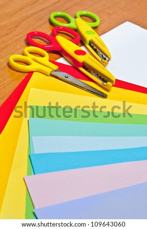 Scissors for children's art on sheets of colored paper