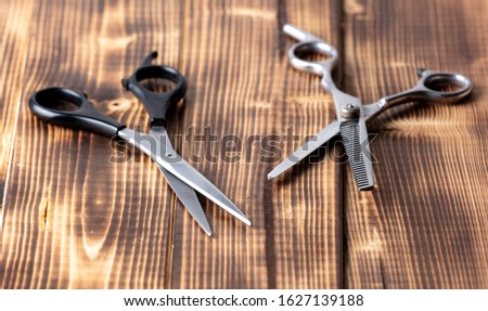 Scissors for haircuts on a wooden background.