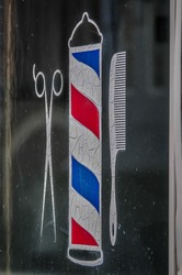 scissors, hair comb and barber sign etched on window