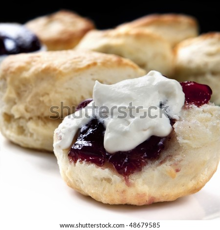 Scone with strawberry jam and cream.  Home-baked, with uncut scones behind.