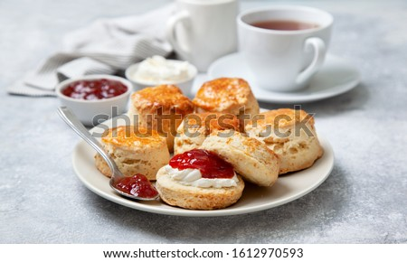 scones on a white plate, a jar of strawberry jam and a cup of tea on a gray background Stock photo ©