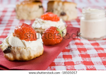 Scones, strawberries and clotted cream on a red napkin - stock photo