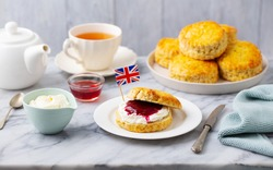 Scones, tea cakes with jam, clotted cream with the flag of Great Britain. Traditional British teatime. Grey background.