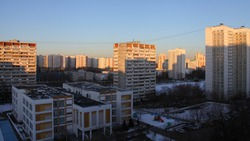 Scool and multi-storey residential buildings with in the Moscow district of Konkovo on a winter morning in the sun rays