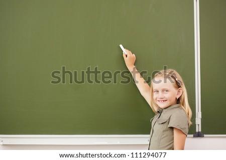 Scoolgirl standing in class near a green blackboard - stock photo
