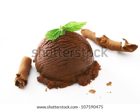 Scoop of rich creamy chocolate ice cream dessert topped with fresh mint and served with shavings