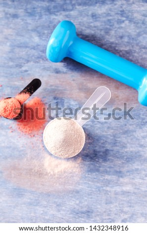 Scoop of Whey Protein, Creatine Powder and a blue Dumbbell in background. Sport nutrition. Rustic wooden background. Top view.  Copy space