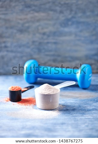 Scoop of Whey Protein, Creatine Powder and blue Dumbbell in background. Sport nutrition. Rustic wooden background. Close up. Copy space