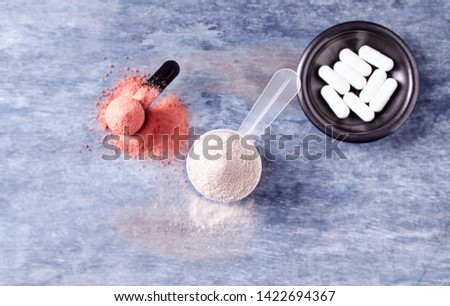 Scoop of Whey Protein, Creatine Powder and Taurine capsules. Sport nutrition. Rustic wooden background. Top view. Copy space