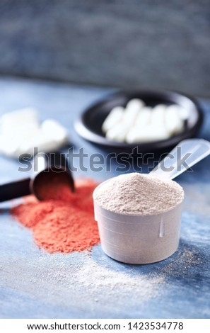 Scoop of Whey Protein, Creatine Powder and Taurine capsules. Sport nutrition. Rustic wooden background. Close up. Copy space