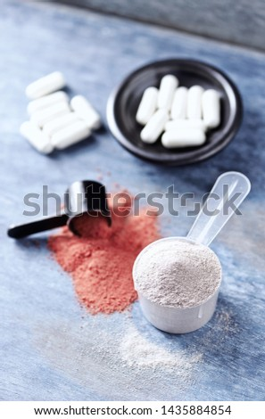 Scoop of Whey Protein, Creatine Powder and Taurine capsules. Sport nutrition. Rustic wooden background. Copy space