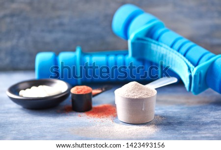 Scoop of Whey Protein, Creatine Powder, Taurine capsules and blue Dumbbells in background. Sport nutrition. Rustic wooden background. Close up. Copy space