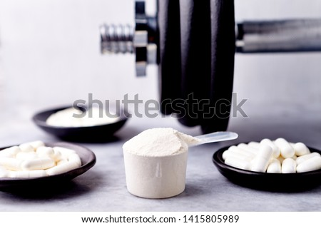 Scoop of Whey Protein, Creatine, Taurine, Beta Alanine capsules and a dumbbell. Bodybuilding food supplements on stone / wooden background. Close up. Copy space.