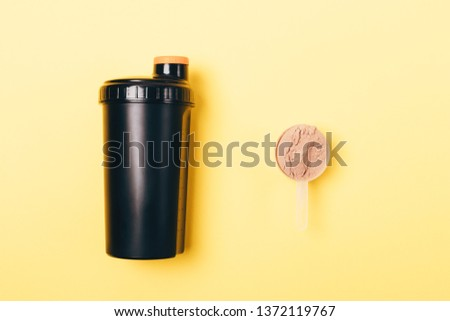 Scoop of whey protein powder near shaker for sports drink on yellow background, top view.